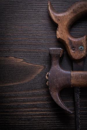 serrucho: Composición de sierra de mano grunge y el martillo de orejas en tablero de madera.