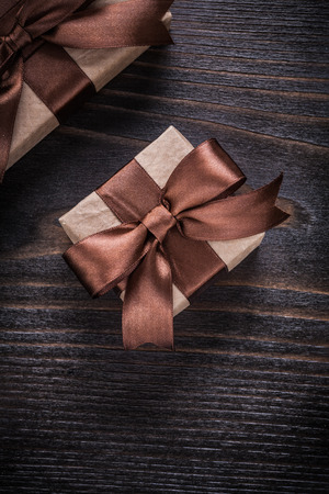 boxed: Boxed presents with brown ribbons on vintage wood board.