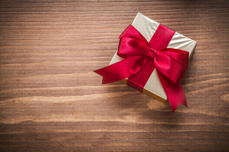 red glittery: Packed glittery gold gift container on vintage wooden board.