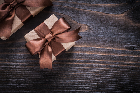 boxed: Boxed gifts with brown ribbons on vintage wood board. Stock Photo