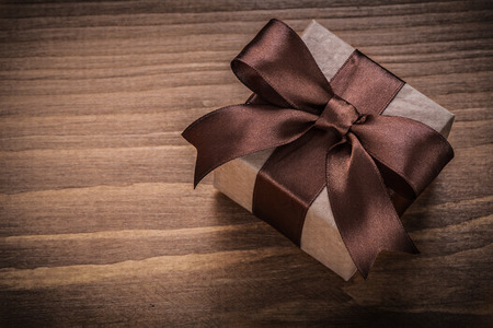 wrapped present: Wrapped present on vintage wood board Stock Photo