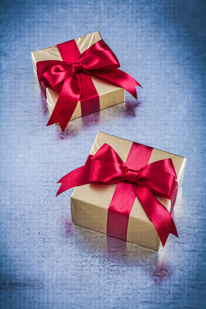 wrapped gift: Boxed golden gifts with red bow on scratched metallic background.