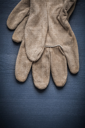 working gloves: pair of working gloves on wooden board.