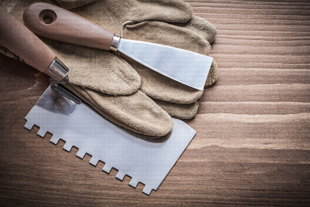 patching: paint scraper and putty knife with working glove. Stock Photo
