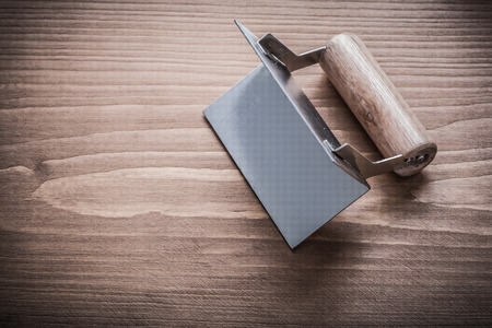 the former: former with wooden handle on wood board. Stock Photo