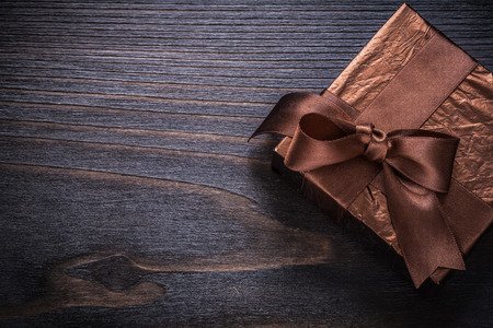 glittery: Boxed present wrapped in glittery paper on vintage wood board. Stock Photo