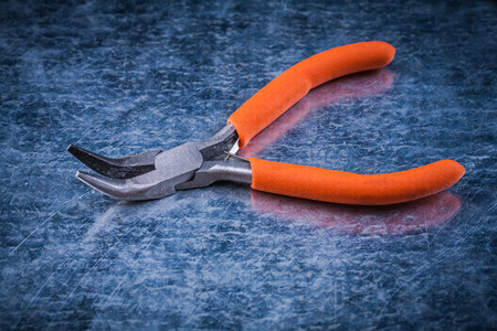 scratched: Insulated electric pliers on scratched metallic background Stock Photo