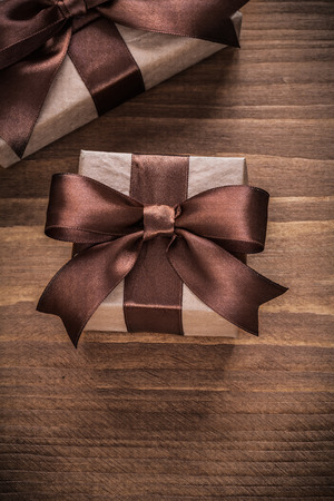 boxed: Boxed present containers with brown ribbons on vintage wooden board.