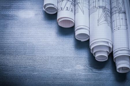 rolls of blueprints on blue board.