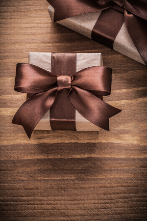 boxed: Boxed gift containers with brown ribbons on vintage wooden board.