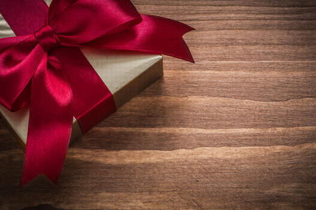 red glittery: Glittery gold giftbox with red ribbon on vintage wooden board. Stock Photo