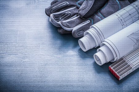 working gloves: rolled blueprints wooden meter and protective working gloves. Stock Photo