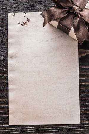 boxed: Boxed present paper on vintage wooden board vertical view. Foto de archivo