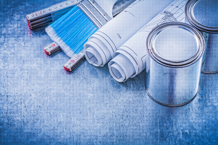 blueprint: Close up view of paint brushes cans blueprints wooden meter.