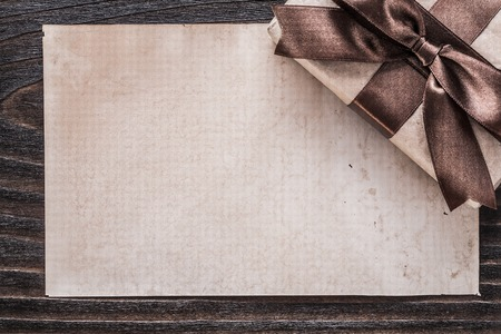 boxed: Boxed present with tied bow paper on vintage wooden board.