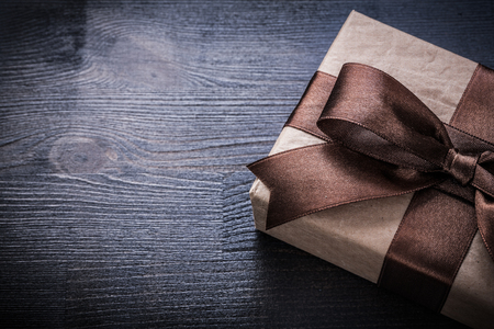 wooden surface: Gift box-container with brown tied ribbon on vintage wooden surface.