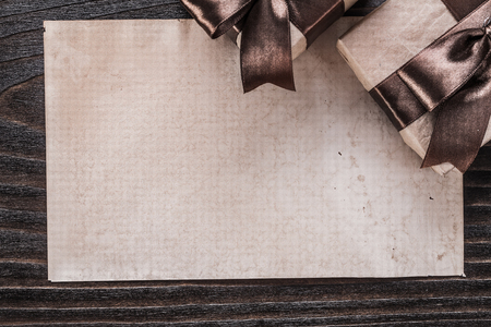 boxed: Boxed gifts with tied brown bows paper on wooden board. Foto de archivo