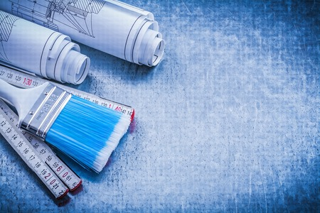 repaint: Paintbrush wooden meter construction drawings on metallic background copyspace.