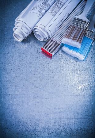 repaint: Paintbrushes wooden meter blueprints on metallic background vertical view.