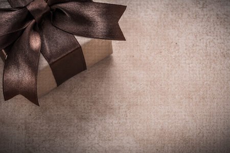 giftbox: Giftbox with tied brown bow paper on vintage background.