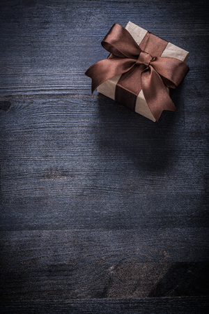 boxed: Boxed present with tied bow on vintage wood board copyspace. Foto de archivo