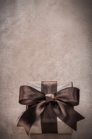wrapped gift: Wrapped gift box with tied ribbon paper on vintage background.
