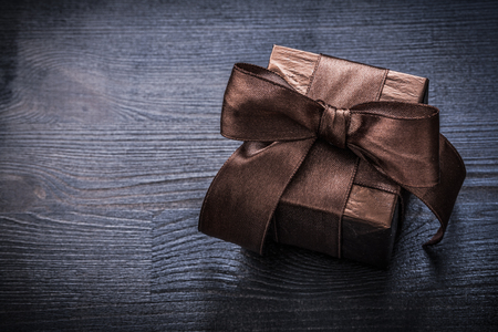 giftbox: Wrapped giftbox shining paper on vintage wooden board holiday concept. Stock Photo