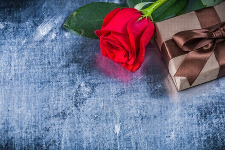 expanded: Red rose giftbox on scratched metallic background holiday concept. Stock Photo