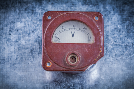scratched: Voltmeter on scratched metallic background vintage electricity concept.