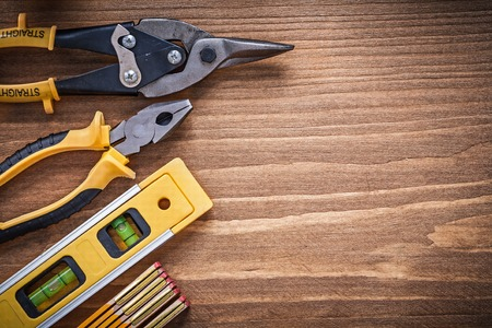 manual measuring instrument: Pliers tin snips construction level wooden meter on wood board.