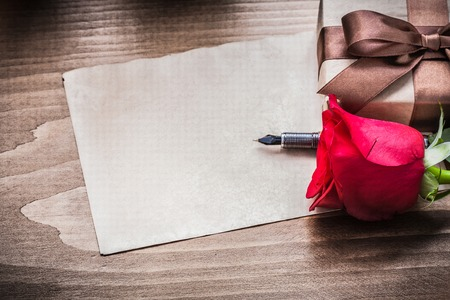giftbox: Red rose giftbox sheet of paper fountain pen holiday concept.