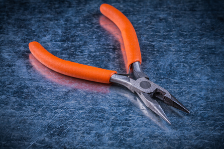 gripping: Insulated electric metal gripping tongs on metallic background electricity concept.