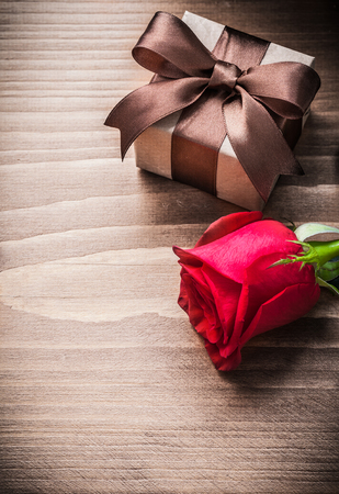 giftbox: Giftbox with bow red rosebud on wooden board holiday concept.