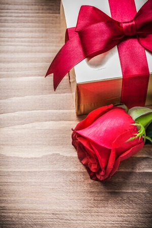 flower boxes: Boxed present with tied bow expanded rose on wooden board.