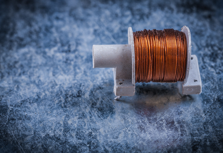 scratched: Transformer with copper wire on scratched metallic background.