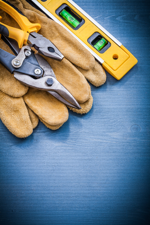 construction level: Pliers steel cutter construction level safety gloves on wooden board.