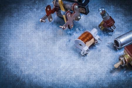 resistor: Electric condenser resistor transformer lamp-holder toggle on scratched metallic background.