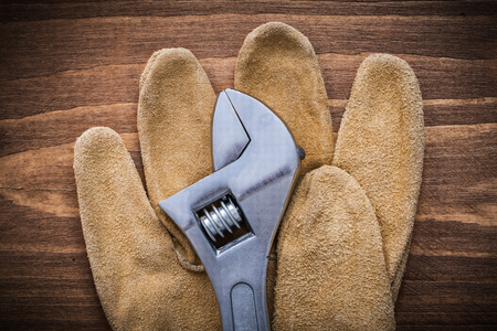 adjustable spanner: Adjustable spanner leather protective gloves on wooden board construction concept. Stock Photo