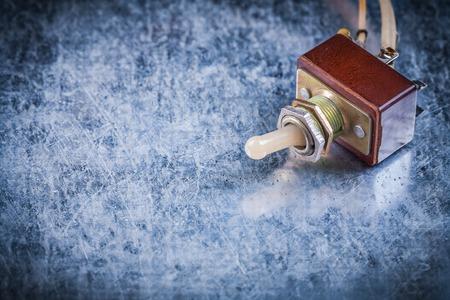 toggle switch: Electric toggle switch on scratched metallic background copyspace image.
