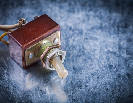 toggle switch: Electric toggle switch on scratched metallic background.