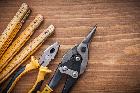 manual measuring instrument: Top view of steel cutter pliers wooden meter construction concept. Stock Photo