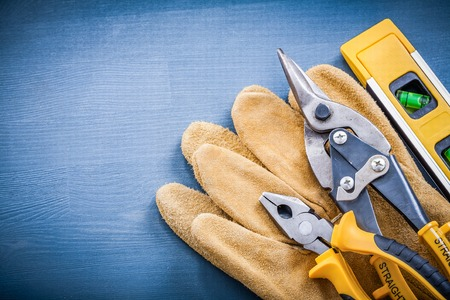 snips: Pliers tin snips construction level safety gloves on wooden board.