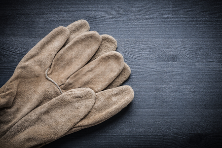 protective gloves: two protective gloves on dark wood board.