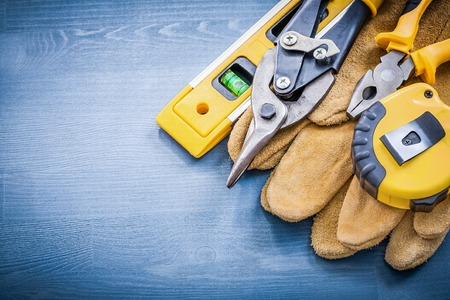 snips: Pliers tin snips tape-measure construction level safety gloves.