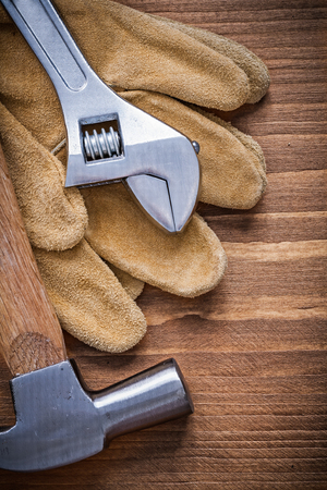 claw hammer: Adjustable spanner claw hammer protective gloves on wooden board.