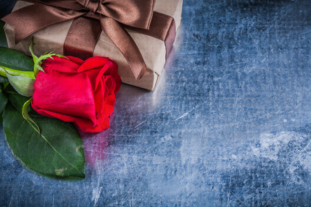 wrapped gift: Natural red rose wrapped gift box on scratched metallic background. Stock Photo