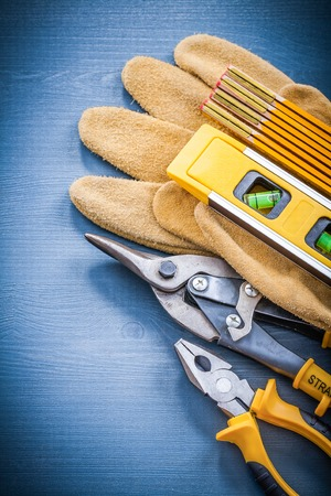 construction level: Pliers tin snips wooden meter construction level protective gloves.