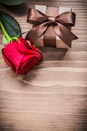 expanded: Giftbox with bow expanded rose on wooden board holiday concept.