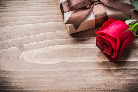 boxed: Boxed present expanded rose head on wooden board holiday concept.