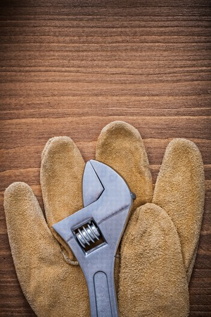close up  wrench: Adjustable key leather protective gloves on wood board construction concept.
